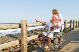 disabled traveler wheelchair couple senior water boardwalk beach sea